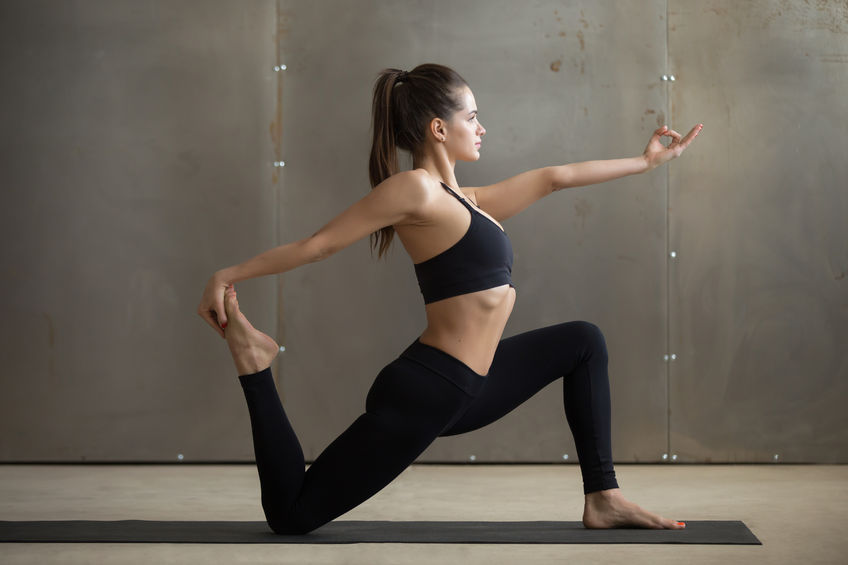 practising yoga, standing in horse rider exercise, anjaneyasana pose, working out, wearing black sportswear, cool urban style, full length, grey studio background, side view Half Kneeling Hip Flexor Stretch | Dr Ken Nakamura Best Toronto Chiropractor